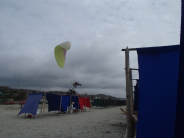 A paraglider taking off from the beach - a common sight in Canoa